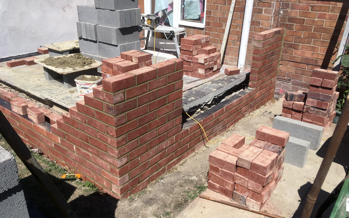 Extension in progress of being built showing stacked bricks